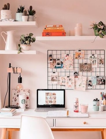 An image of a nicely decorated desk with a laptop and polaroid pictures on the wall.