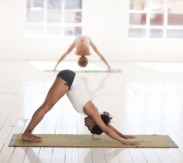 A picture of two women doing yoga for workplace wellness.