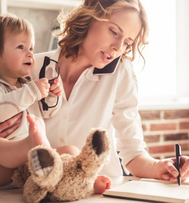 Busy PR agent holds child while making a phone call and writes down notes while working from home.